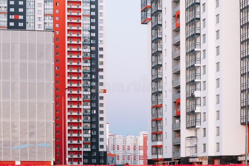 A fachada de um prédio com as listras brancas e cinzentas vermelhas construção do Multi-andar contra o céu azul Fundo a imagem de stock