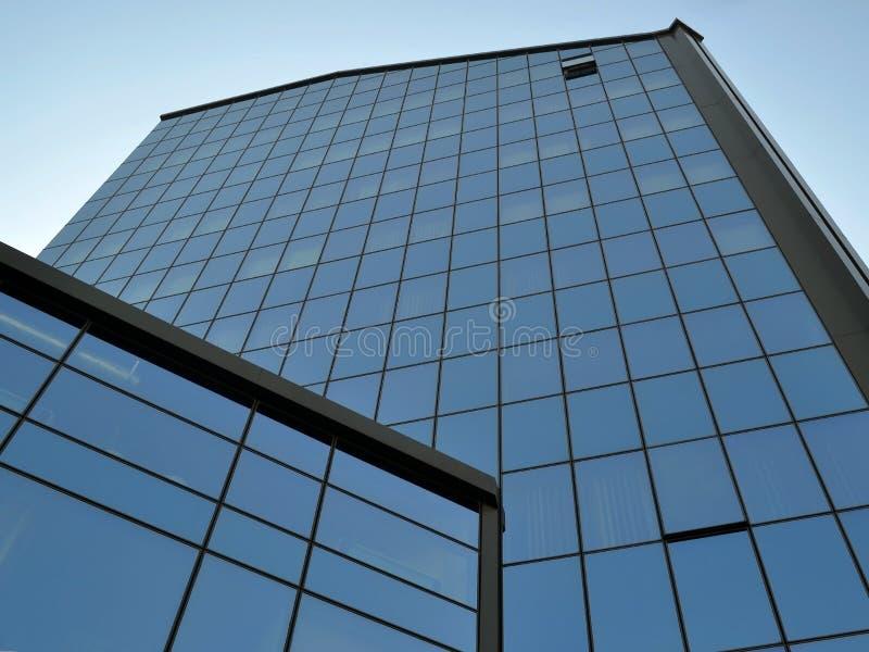 Fachada de um prédio de escritórios moderno feito do vidro e do concreto com as janelas do espelho contra o céu azul do verão em  foto de stock royalty free
