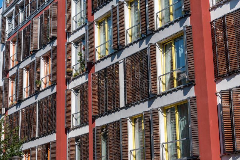 A fachada de uma casa de apartamento moderna com janelas de madeira shutters imagens de stock royalty free