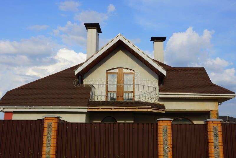 Fachada de uma casa com um balcão sob um telhado marrom imagem de stock royalty free