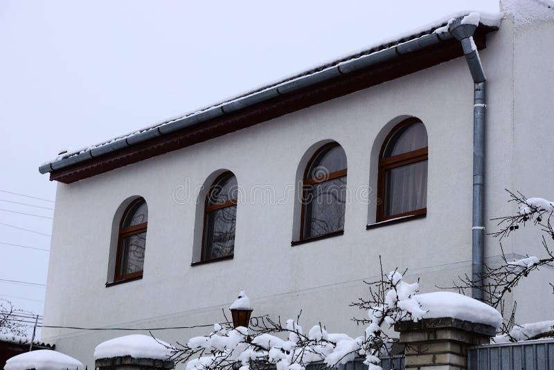 Fachada de uma casa privada cinzenta com janelas com um telhado sob a neve branca contra o céu imagem de stock