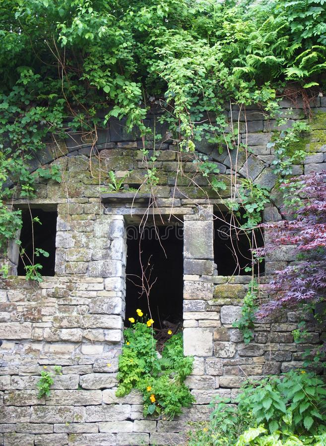 Fachada de uma casa rural de pedra abandonada com janelas vazias e a entrada cobertos de vegetação com as ervas daninhas colorida imagens de stock royalty free