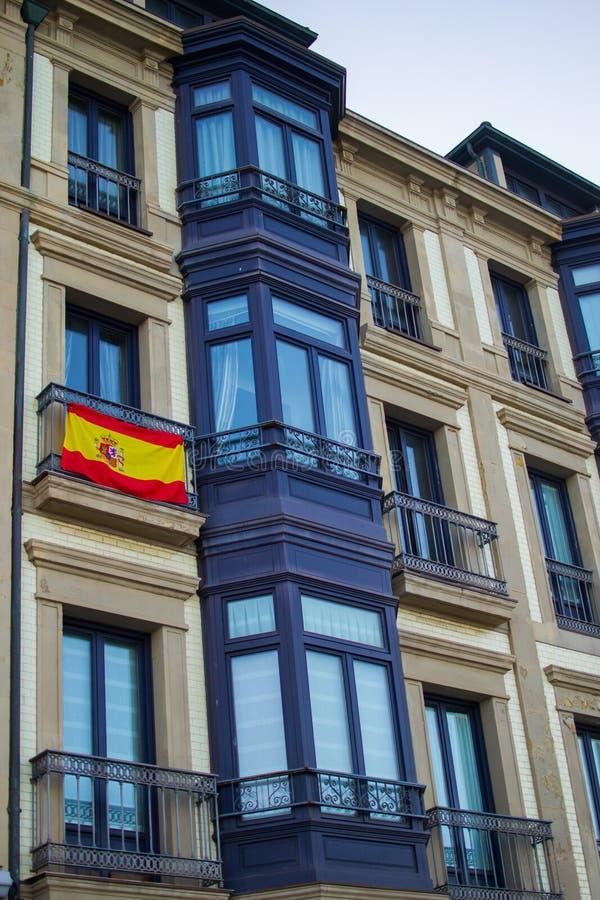 Fachada de uma construção clássica com a bandeira espanhola em uma de suas janelas Espanha em Gijon, as Astúrias foto de stock