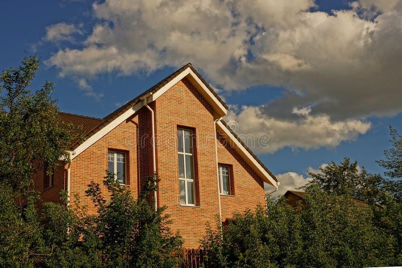 Fachada de uma construção de tijolo com as janelas em árvores verdes e os arbustos no jardim imagens de stock royalty free