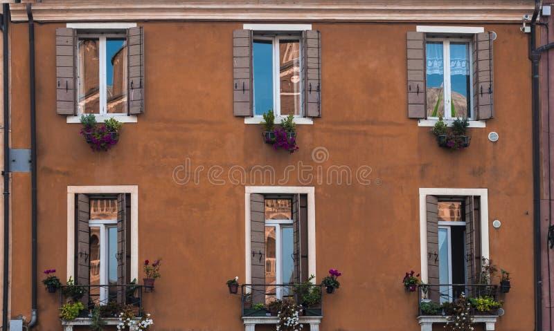 Fachada de un edificio residencial en Padua, Italia Windows, obturadores y balcones con las flores foto de archivo libre de regalías
