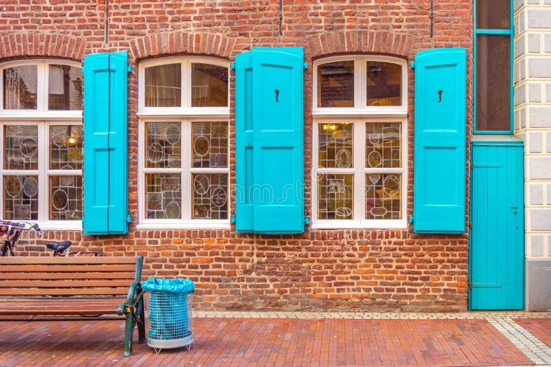 Fachada de una casa alemana Ventanas con persianas azules Puerta azul Basura azul Banco de madera fotografía de archivo