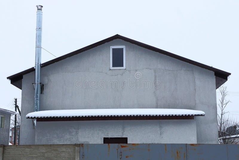 Fachada de una casa gris con una pequeña ventana en el ático con un tejado debajo de la nieve detrás de la cerca imagen de archivo