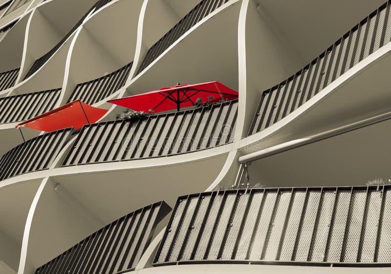 Fachada de una casa residencial con los parasoles rojos imagenes de archivo