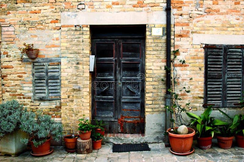 Fachada de una casa vieja con las plantas en potes delante de ella imagen de archivo