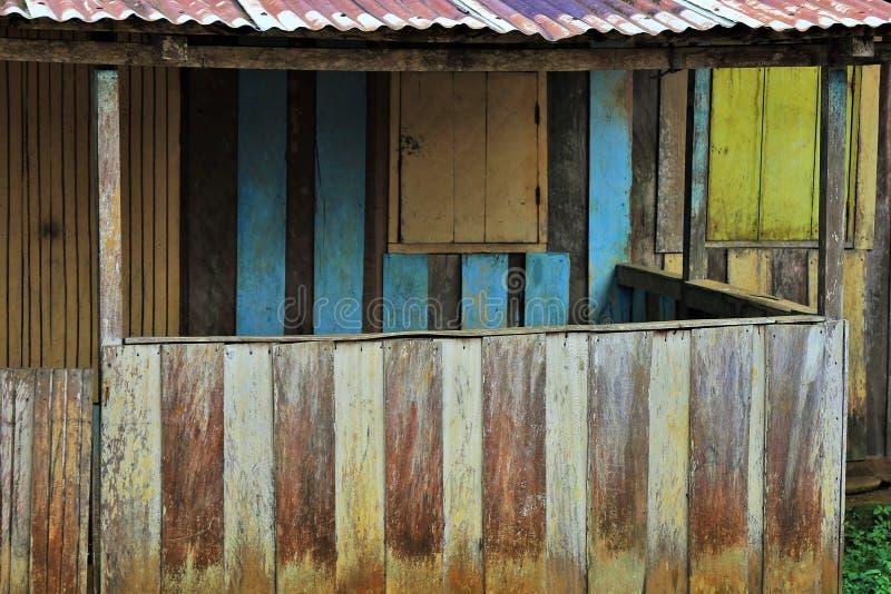 Fachada de una pequeña casa en Gabón, hecha de los tablones de madera de diversos colores imagenes de archivo