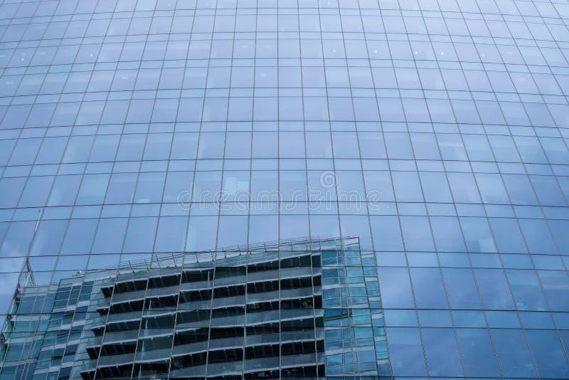 Fachada de vidro da torre de Aldgate na rua principal de Whitechapel, Londres, com reflexão do céu e da construção oposto a fotografia de stock