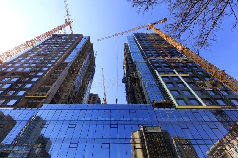 A fachada de vidro, uma reflexão do céu azul e guindastes perto de uma construção concreta moderna sob a construção foto de stock