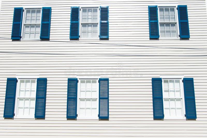 Fachada del edificio con la pared de madera blanca, las ventanas y los obturadores azules en Key West, los E.E.U.U. Arquitectura  fotografía de archivo