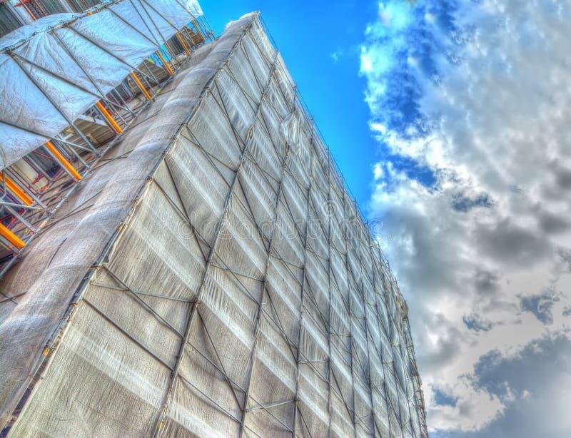 Fachada del edificio cubierta para el trabajo de la restauración debajo de un cielo nublado foto de archivo libre de regalías