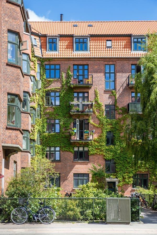 Fachada del edificio de ladrillo rojo con los balcones y la hiedra, Copenhague imagenes de archivo