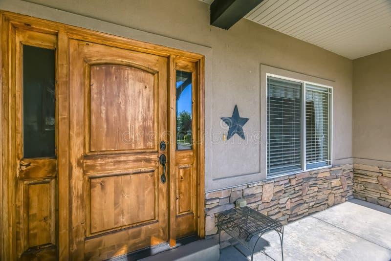 Fachada del hogar con la puerta de madera y el pórtico iluminado por el sol imagenes de archivo