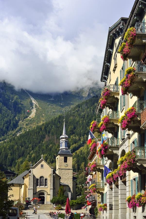 Fachada do hotel e a igreja atrás na cidade Chamonix imagem de stock