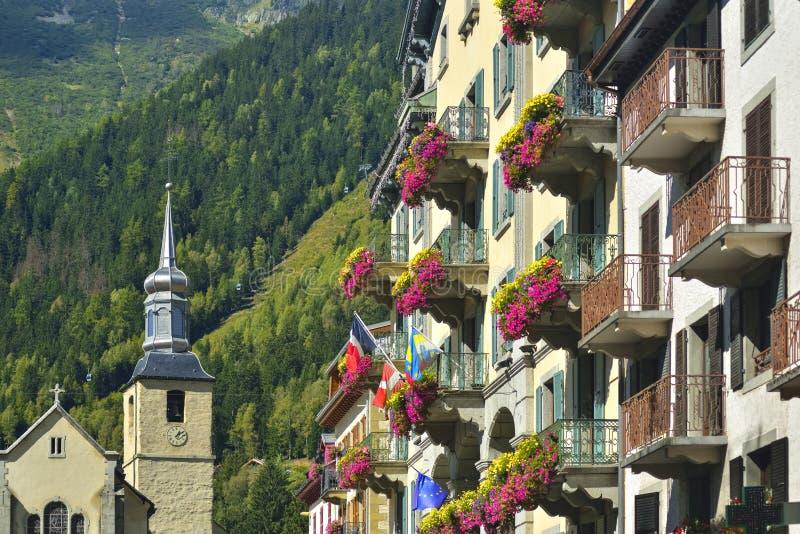 Fachada do hotel e a igreja atrás na cidade Chamonix imagens de stock