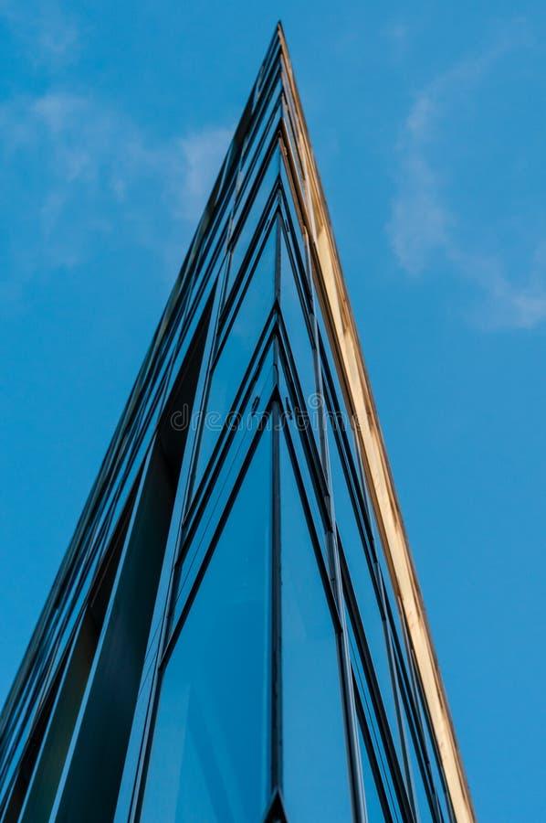 Fachada do prédio de escritórios moderno com vidro e aço sob o céu azul, as reflexões e o foco seletivo foto de stock
