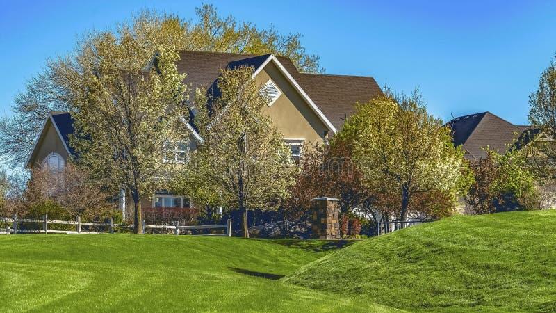 Fachada do quadro do panorama da casa no terreno gramíneo vasto sob o céu azul claro em um dia ensolarado imagens de stock