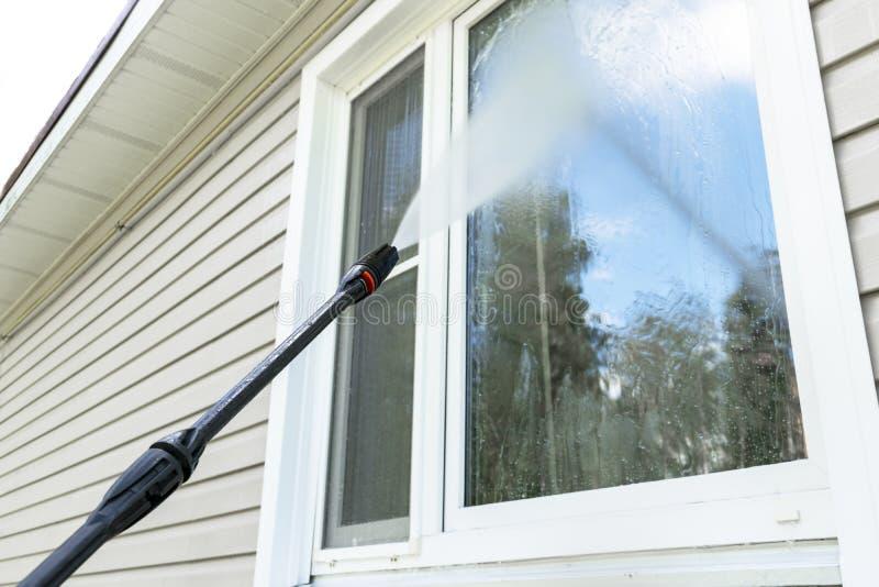 Fachada e janela de limpeza da construção da lavagem do serviço com água da pressão Parede suja de limpeza com o jato de ?gua de  imagens de stock