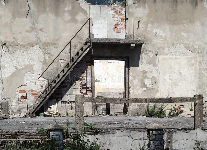 Fachada, entrada y escalera de una casa de dos pisos abandonada y arruinada imagenes de archivo