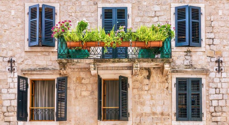 Fachada europea bonita de la casa, con los obturadores de la ventana, el balcón, y las plantas en conserva fotos de archivo