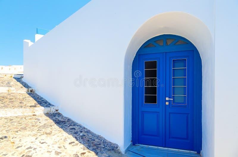 Fachada grega branca tradicional da casa com porta azul Santorini, Grécia fotografia de stock royalty free