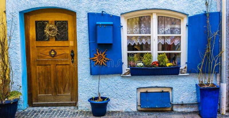 Fachada hermosa de la casa con la puerta, los obturadores y flo de madera fotos de archivo