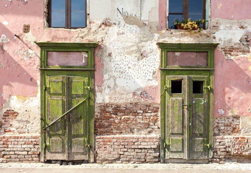 Fachada lascando-se velha com as duas portas fechados fotos de stock