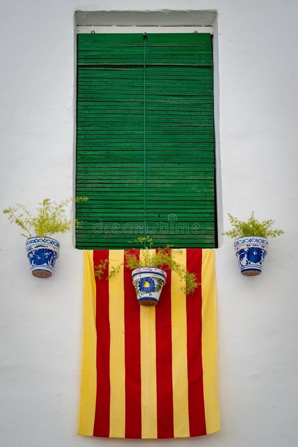 Fachada mediterrânea típica com janela, vasos de flores e a bandeira catalan nacional imagem de stock