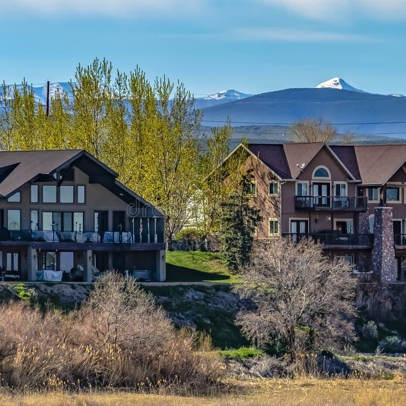 Fachada quadrada do quadro de casas bonitas com montanhas e fundo nebuloso do céu azul imagem de stock