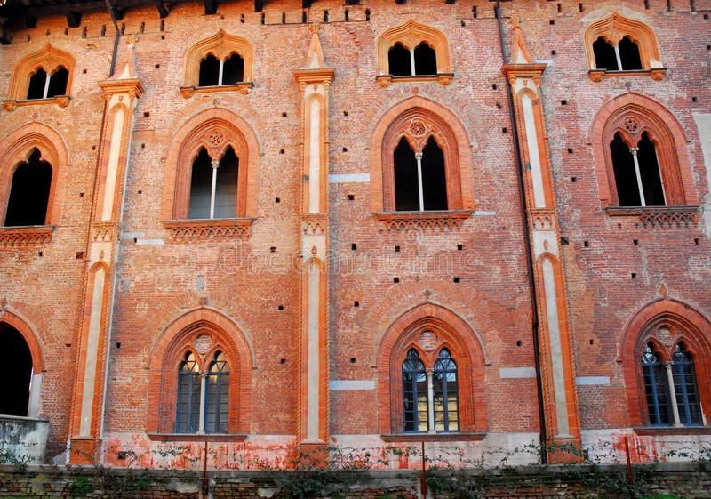 Fachada roja con nueve ventanas divididas con parteluz maravillosas en el castillo de Vigevano cerca de Pavía en Lombardía (Itali fotografía de archivo libre de regalías