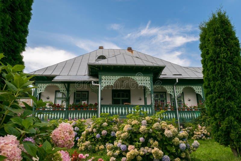 A fachada romena típica velha da casa com verde pintou as portas de madeira, as janelas e o pátio de entrada coberto imagem de stock royalty free