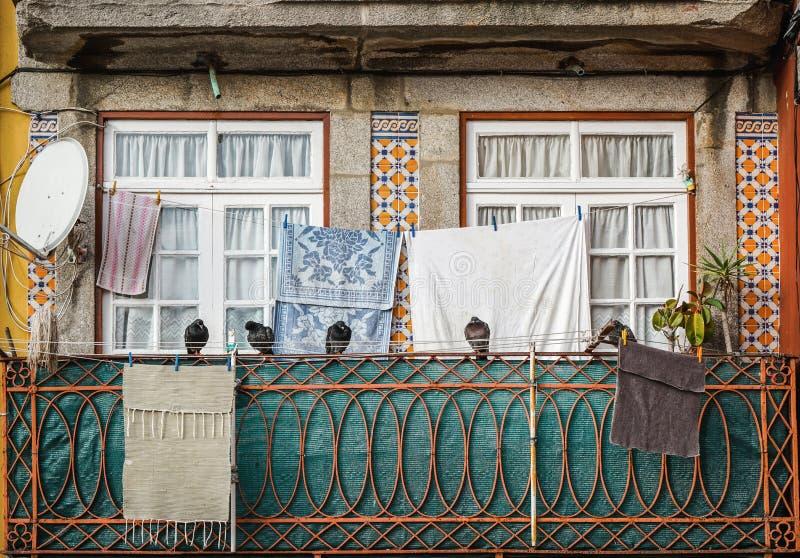 Fachada tradicional del edificio y de las ventanas viejos con la ropa que cuelga de cuerda para tender la ropa y de palomas en fi fotografía de archivo