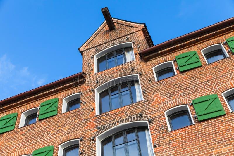 Fachada velha da casa, parede de tijolo vermelho com janelas imagem de stock