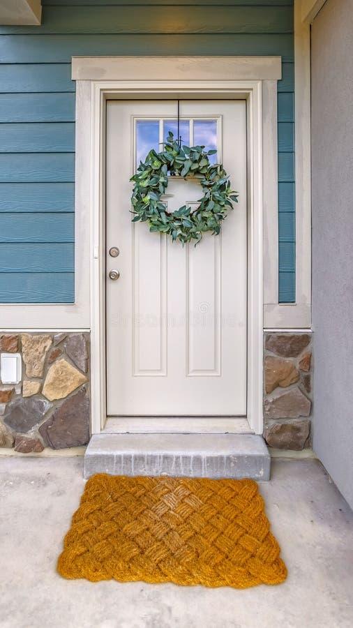 Fachada vertical clara de un hogar con una guirnalda frondosa simple que cuelga en la puerta principal blanca imagen de archivo
