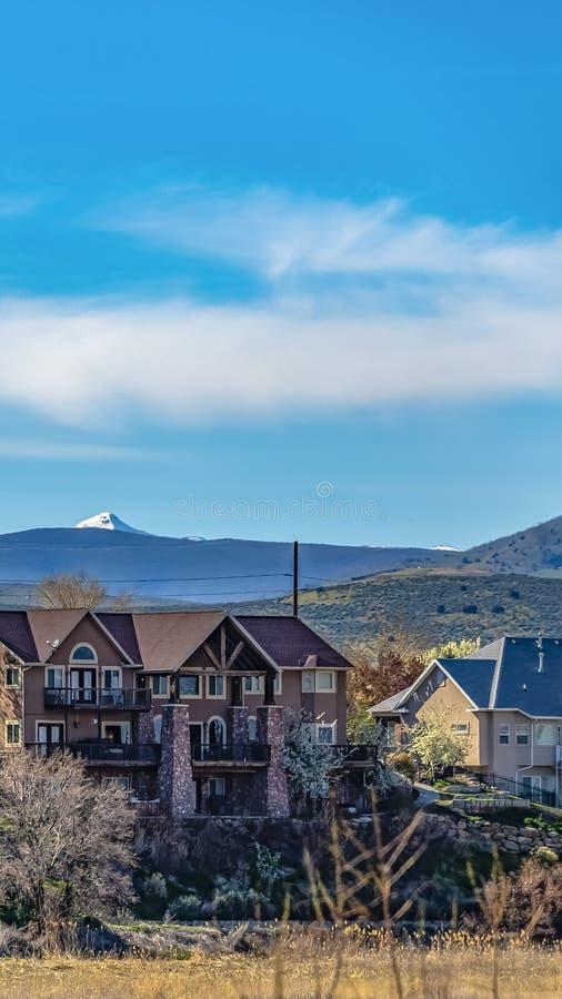 Fachada vertical de casas bonitas com montanhas e fundo nebuloso do céu azul fotos de stock royalty free