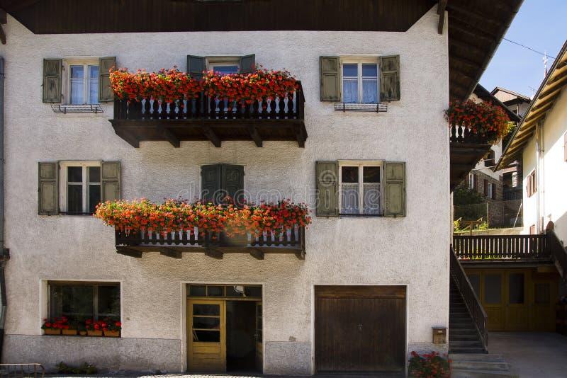 Fachada y flores, Nova Levante, Italia imagen de archivo