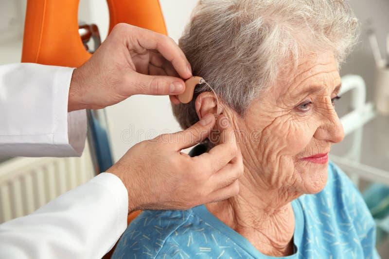 Facharzt für Hals- und Ohrenleiden, der Hörgerät in das Ohr des älteren Patienten einsetzt stockfoto