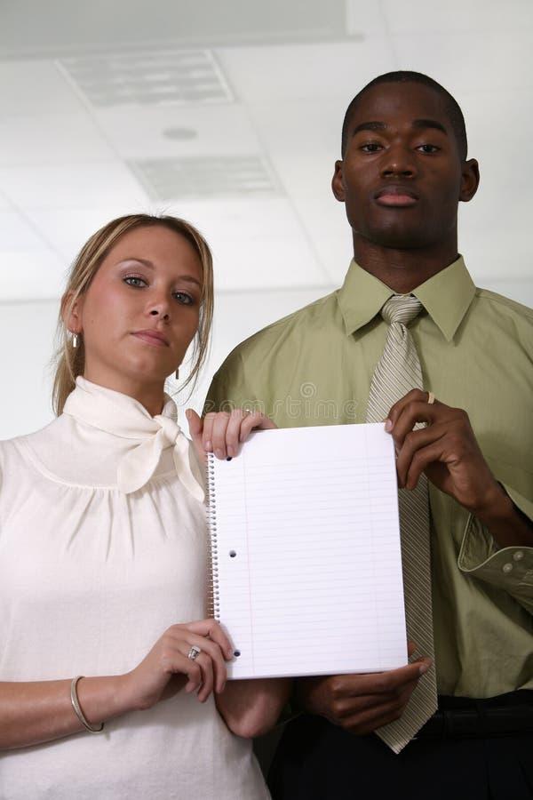 Fachleute, die unbelegtes weißes Notizbuch anhalten stockbilder