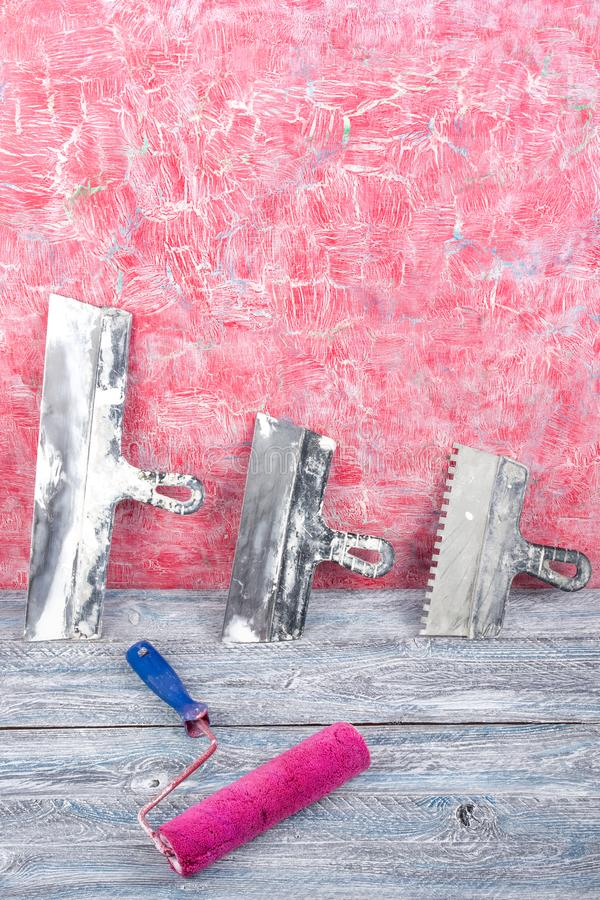 Fachmann, der Werkzeuge für Verzierungsund errichtenden Erneuerungssatz, Wand im Hintergrund repariert Vergipsen der Hilfsmittel stockfotos