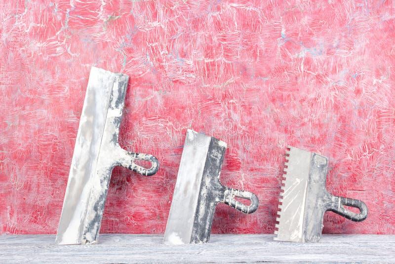 Fachmann, der Werkzeuge für Verzierungsund errichtenden Erneuerungssatz, Wand im Hintergrund repariert Vergipsen der Hilfsmittel lizenzfreies stockfoto
