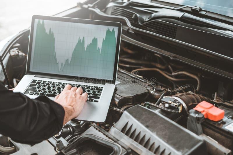 Fachmonteur Hands der Prüfung des Automotorreparaturservices unter Verwendung des Laptops auf Auto stockfoto