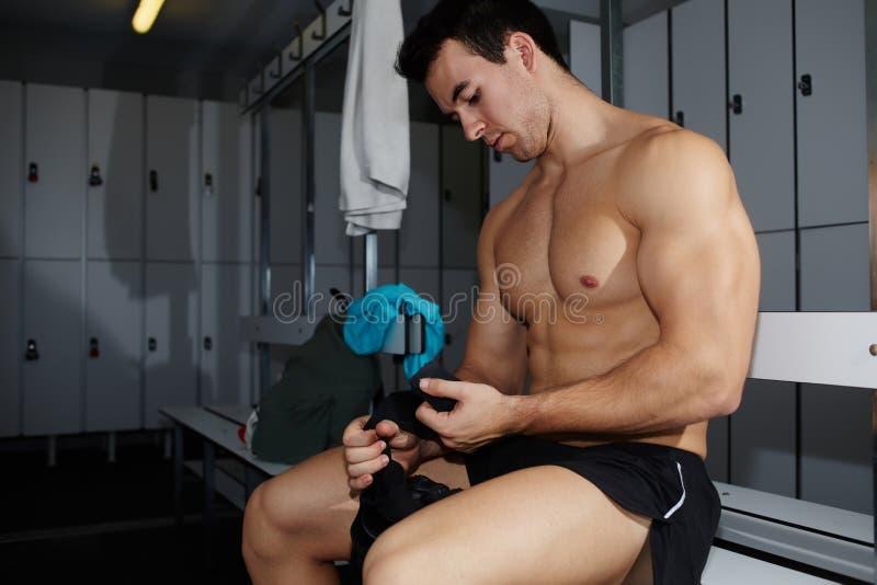 Fachowa atleta usuwa ciężaru udźwigu rękawiczki siedzi w gym szatni fotografia royalty free