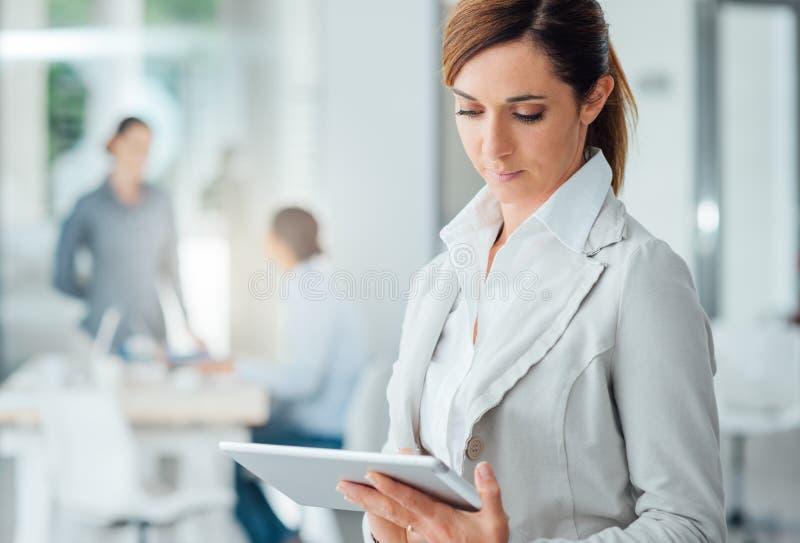 Fachowa biznesowa kobieta używa cyfrową pastylkę fotografia stock
