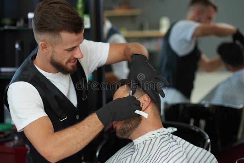 Fachowa fryzjera męskiego golenia twarz klient z żyletką zdjęcia stock
