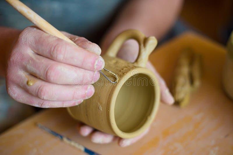 Fachowa garncarka robi wzorowi na glinianym kubku z specjalnym narzędziem w garncarstwie fotografia stock