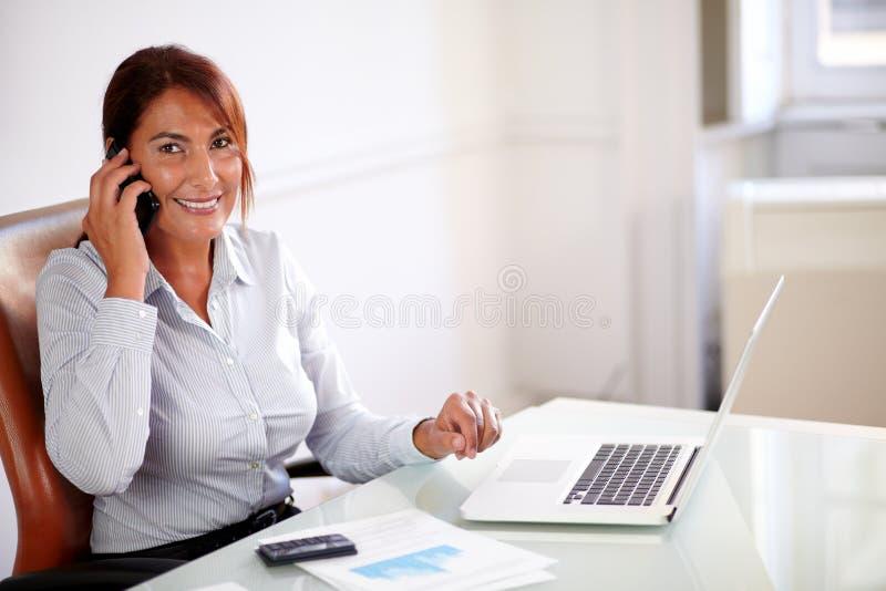 Fachowa kobieta conversing na jej komórce obraz royalty free