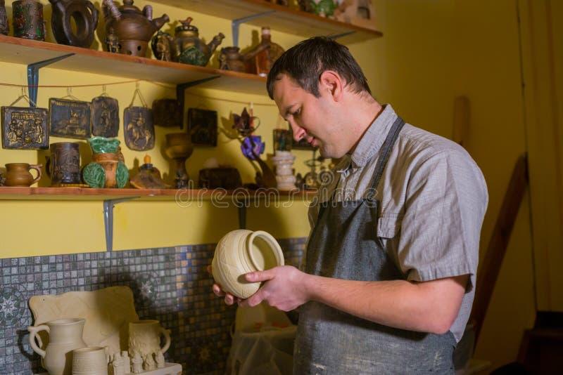 Fachowa męska garncarka egzamininuje garnek w ceramicznym warsztacie fotografia stock